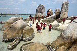 Wisatawan berfoto di antara gugusan batu granit di Pulau Batu Belayar di Belitung, Kepulauan Bangka Belitung. Pemerintah setempat terus mendorong potensi wisata Belitung yang memiliki keindahan permukaan laut dengan bebatuan granitnya, guna meraih status Unesco Global Geopark di 2019.