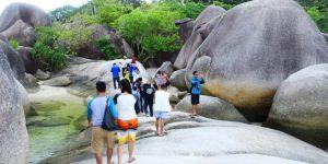 wisatawan berjalan di tepi pantai di antara bebatuan granit